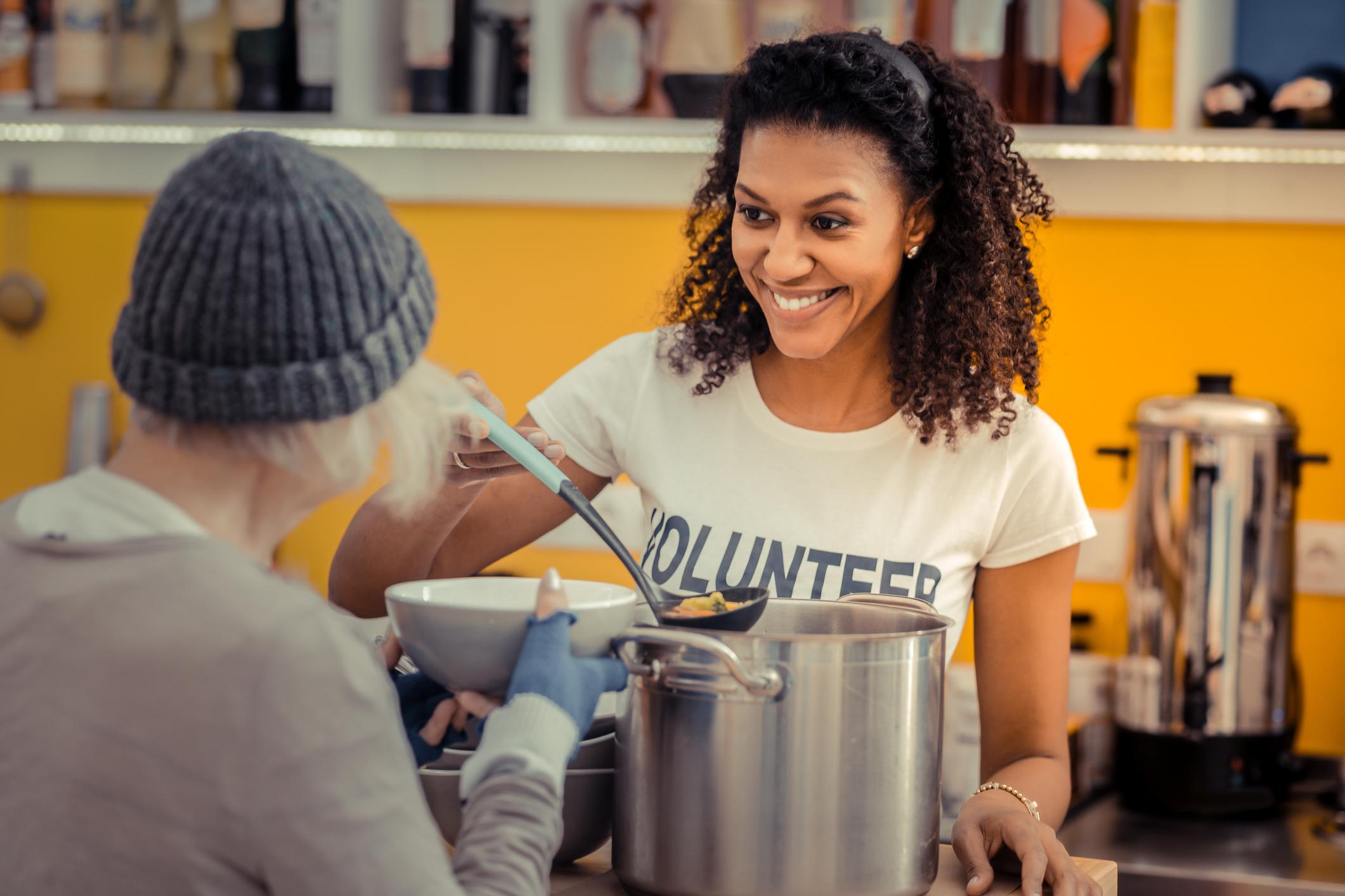 Woman serving Soup to a homeless woman