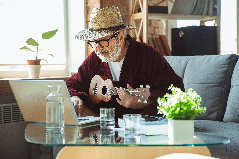 Elderly man playing ukulele over video chat