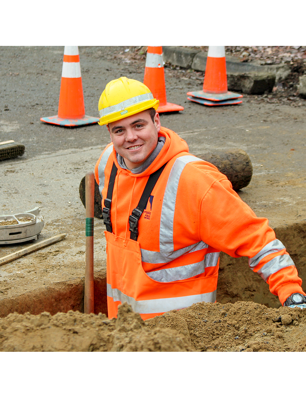 Smiling City worker in a hole