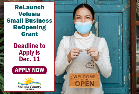 female holding a 'we are open' sign with text that says the deadline to apply for the grant is december 11