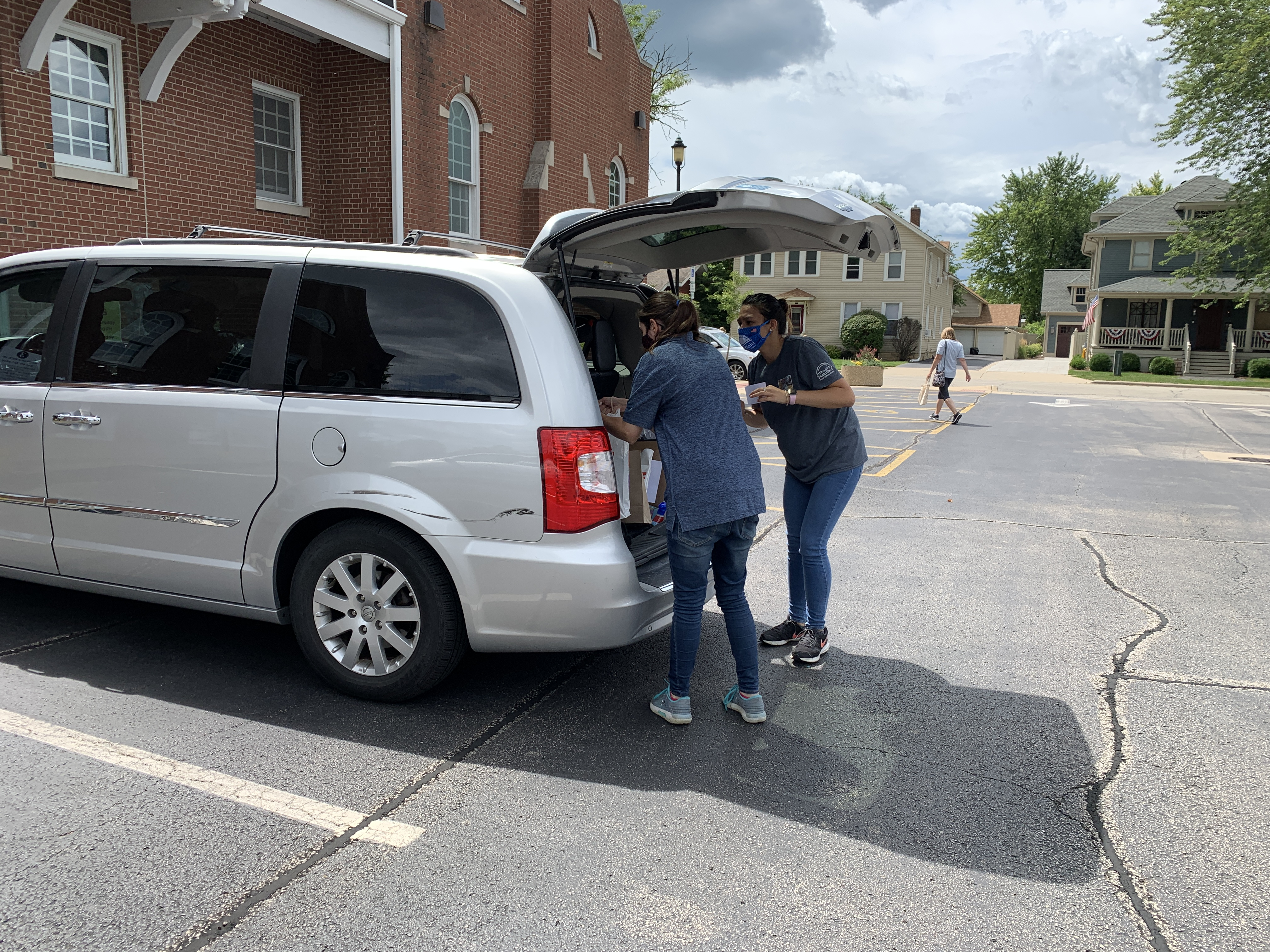 Staff loading a car with materials during curbside delivery