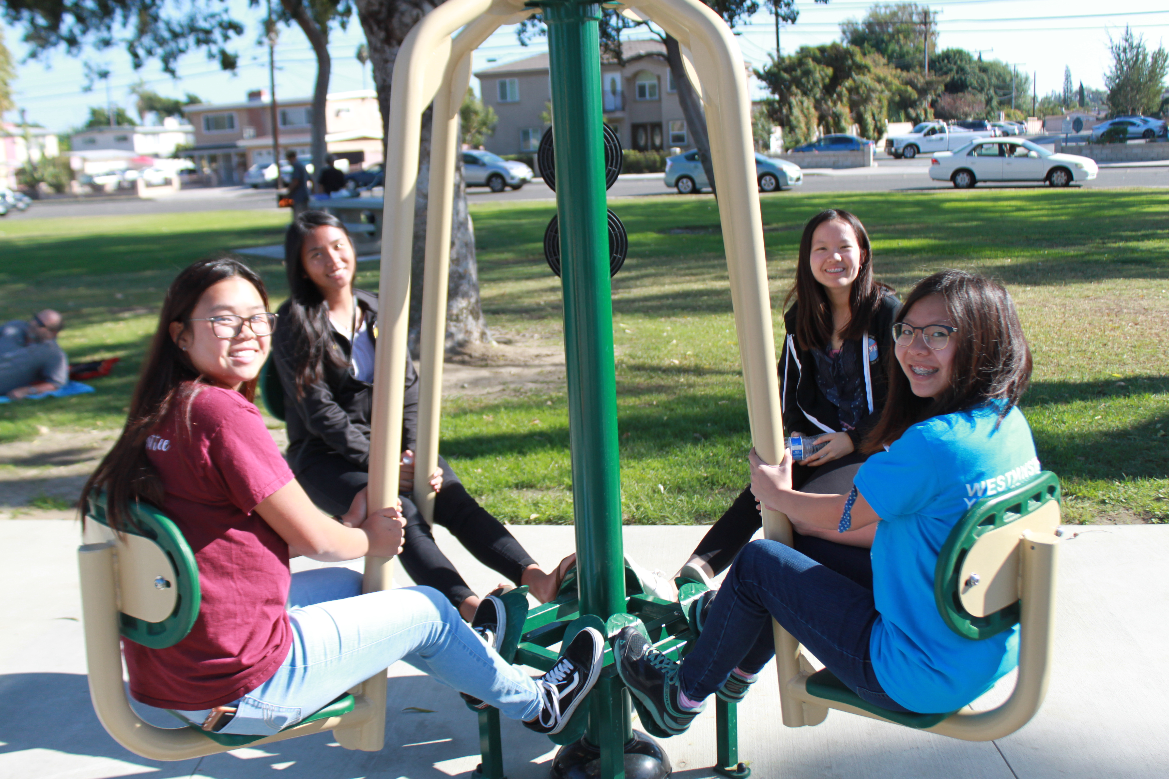 Smiling teenagers using outdoor exercise equipment